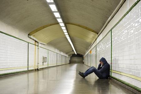 emotional pain: Hombre joven en una campana abandonado perdi� en la depresi�n que se sienta en la calle de tierra t�nel del metro que sufren dolor emocional, tristeza y mirando destruido y desesperado apoyado en la pared solo
