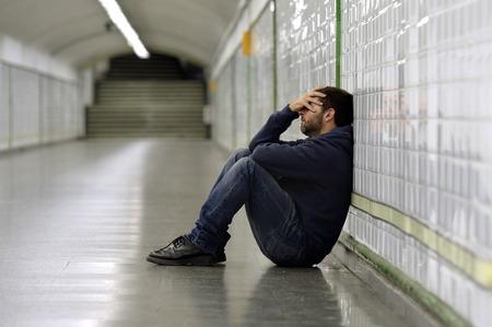 emotional pain: Hombre joven abandon� perdido en la depresi�n que se sienta en la calle de tierra t�nel del metro que sufren dolor emocional, tristeza y mirando inclinada enferma y desesperada en la pared solo