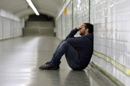 Young man abandoned lost in depression sitting on ground street subway tunnel suffering emotional pain, sadness and looking sick and desperate leaning on wall alone
