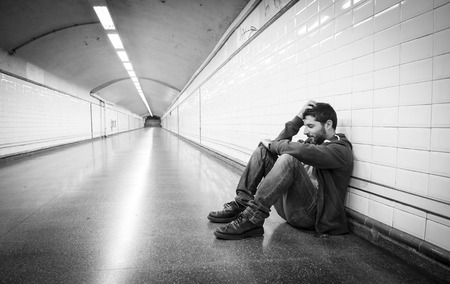 desperate face: Young man abandoned lost in depression sitting on ground street subway tunnel suffering emotional pain, sadness and looking destroyed and desperate leaning on wall alone  Stock Photo