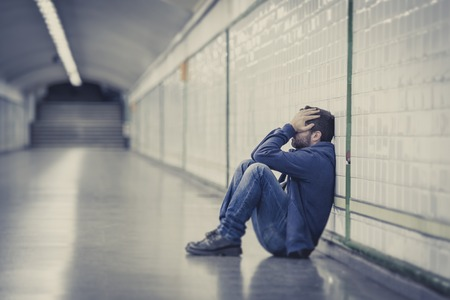 addiction alone: Young man abandoned lost in depression sitting on ground street subway tunnel suffering emotional pain, sadness and looking destroyed and desperate leaning on wall alone  Stock Photo