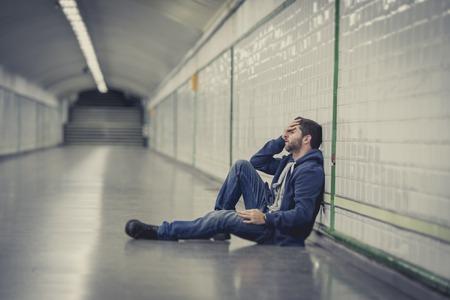 Jonge man verlaten verloren in een depressie zitten op de grond straat metrotunnel lijden emotionele pijn, verdriet en op zoek vernietigd en wanhopig leunend op de muur staan Stockfoto