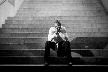 man crying: Young business man crying abandoned lost in depression sitting on ground street concrete stairs suffering emotional pain, sadness, looking sick in grunge lighting