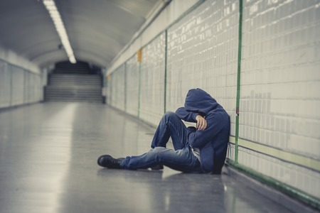 Young man abandoned lost in depression sitting on ground street subway tunnel suffering emotional pain, sadness and looking destroyed and desperate leaning on wall alone  스톡 콘텐츠