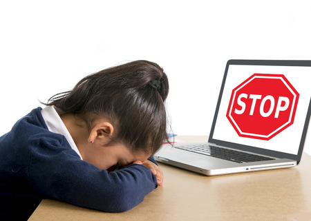 hispanic sweet little girl crying and suffering internet bullying and abuse at school sitting at desk with computer and stop sign Stock Photo