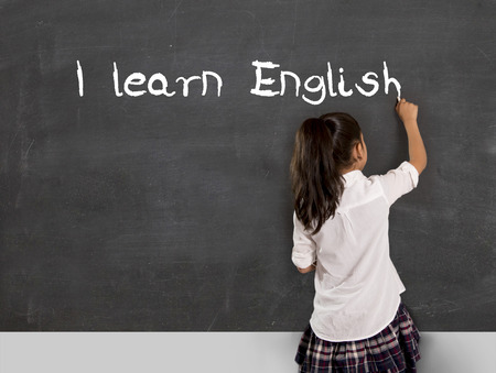 latin language: sweet little Hispanic girl at school lesson with ponytail and uniform writing with chalk on classroom blackboard in English learning , wisdom and successful education concept