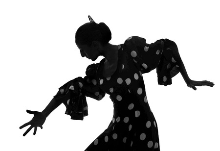 Silhouette of Spanish woman Flamenco dancer dancing Sevillanas in gypsy dots dress