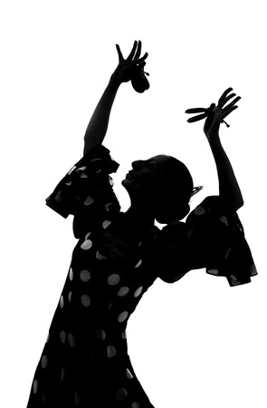 Silhouette of Spanish woman Flamenco dancer dancing Sevillanas in gypsy dots dress  photo