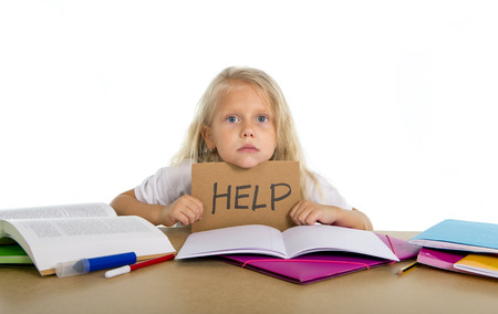 children learning: sweet little blonde hair school girl holding help sign in stress with books and homework Stock Photo