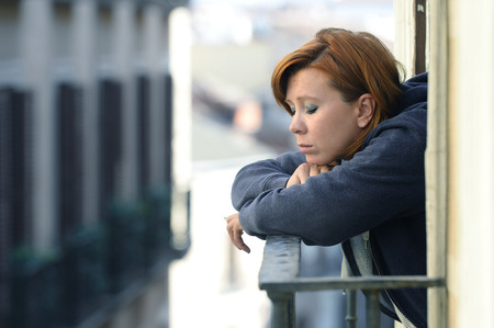 depressed woman: young attractive woman suffering depression and stress smoking outdoors at the balcony window in pain and grief feeling sad and desperate in urban background Stock Photo