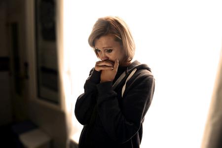 うつ病と痛みと感じて悲しいと絶望的な自宅スタジオ バックライト付きウィンドウに対する悲しみで泣いて一人で立ってストレスに苦しんでいる若 写真素材