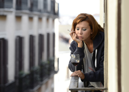 young attractive woman suffering depression and stress smoking drinking glass of wine at the balcony window in pain and grief feeling sad and desperate in urban background photo