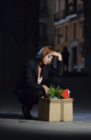young attractive jobless business woman depressed and fired from work with cardboard box office belongings wasted on street after loosing her job, worried and sad photo