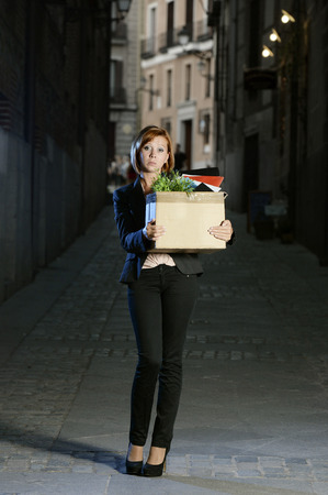 young attractive jobless business woman depressed and fired from work carrying cardboard box office belongings wasted on street after loosing her job, worried and sad photo