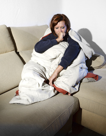 couching: young sick woman sitting on couch wrapped in duvet and blanket feeling miserable and ill couching and suffering a cold at home Stock Photo