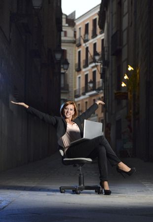 Happy relaxed Business woman office dressed sitting on Chair outdoors on Street with Computer laptop in successful and flexible worker concept on studio lighting  photo