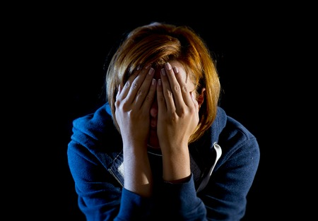 young woman suffering depression and stress sitting alone in pain and grief covering face with hands feeling sad and desperate isolated on black background