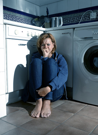 miserable: lonely depressed and sick woman sitting alone crying on kitchen floor in stress suffering depression and sadness feeling miserable in barefoot looking desperate