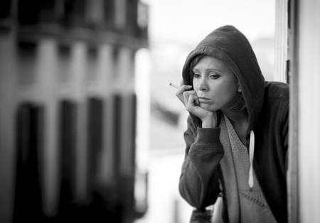 young attractive woman suffering depression and smoking in stress outdoors at home balcony terrace window in pain and grief feeling sad and desperate in urban background in black and white photo