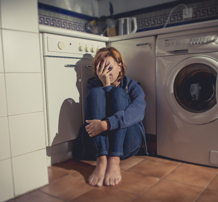 lonely depressed and sick woman sitting alone on kitchen floor in stress , depression and sadness feeling miserable in barefoot looking desperate photo