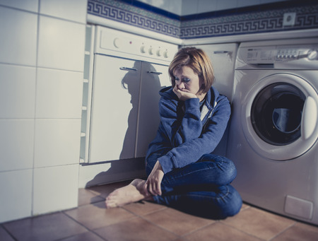 lonely depressed and sick woman sitting alone on kitchen floor in stress , depression and sadness feeling miserable in barefoot looking desperate