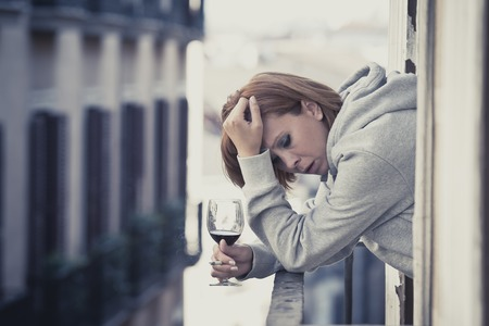 depressed woman: young attractive woman suffering depression smoking and drinking wine in stress outdoors at home balcony terrace window in pain and grief feeling sad and desperate in urban background Stock Photo