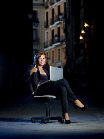 Happy relaxed Business woman office dressed sitting on Chair giving an ok sign outdoors on Street with Computer laptop in successful and flexible worker concept on studio lighting  photo