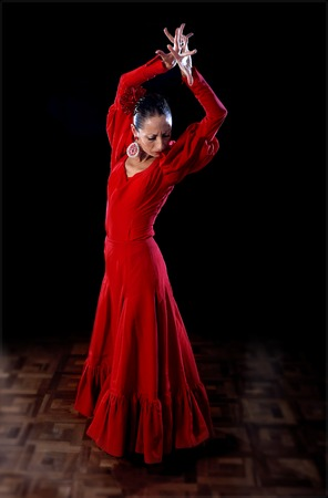 young Spanish woman flamenco dancer dancing Sevillanas show wearing traditional folk red dress in traditional Dance of Spain concept performing show on wooden stage Stock Photo