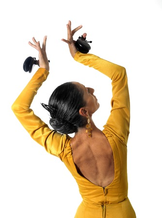 young Spanish woman dancing Sevillanas with castanets in hands wearing yellow dress with open back in flamenco traditional dance of Spain concept isolated on white background