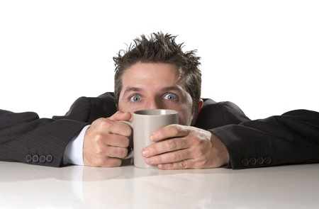 crazed: young addict business man in suit and tie holding cup of coffee anxious and crazy in caffeine addiction and need to keep awaken isolated on white background