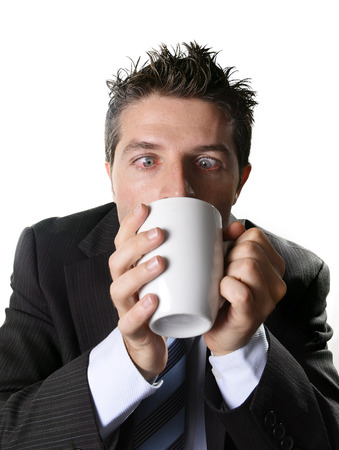 crazed: young addict business man in suit and tie drinking cup of coffee crazy in caffeine addiction and need to keep awake isolated on white background