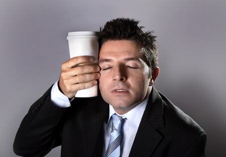 crazed: young  sleepy addict business man in suit and tie holding cup of take away  coffee against sleeping face in caffeine addiction and need to keep awake  isolated on grey