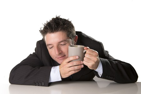 crazed: young sleepy addict business man in suit and tie holding cup of coffee against sleeping face in caffeine addiction and need to keep awake  isolated on white background