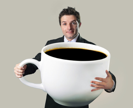 young happy business man holding a funny huge and oversized cup of black coffee in caffeine addiction concept isolated on even background