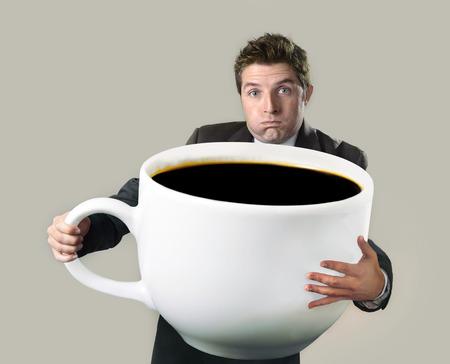 joven hombre de negocios feliz celebración de una taza enorme y de gran tamaño divertido de café negro en concepto de adicción a la cafeína aislada en el fondo incluso Foto de archivo