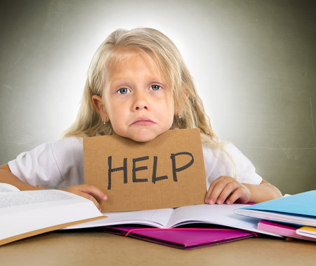 cute little blonde hair schoolgirl sad and frustrated holding help sign in stress with books and homework in children education concept isolated on grunge studio background photo