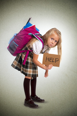 junge blonde Schülerin, die Hilfe Schild Tragen schwerer Rucksack oder Schulranzen voller verursacht Stress und Schmerzen auf dem Rücken durch Übergewicht isoliert auf Grunge-Hintergrund