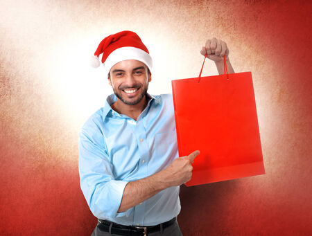 happy young attractive man wearing Santa hat holding and pointing red shopping bag in Christmas sales, consumerism,  buying xmas gifts and presents concept isolated on studio background photo