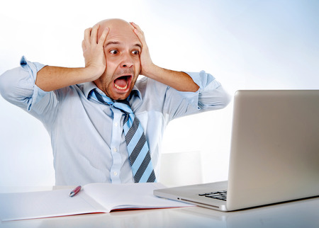bald hispanic overworked frustrated businessman on tie screaming in stress at computer laptop working on office worried about financial crisis or making a huge mistake photo