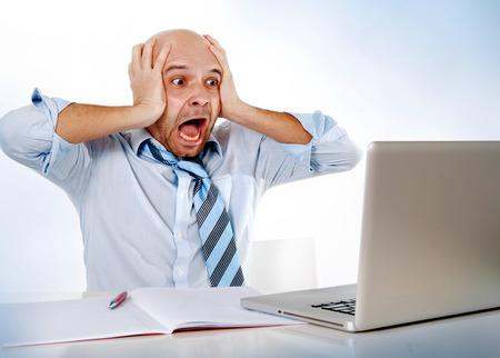 laptop computers: calvo ispanica uomo d'affari frustrato sovraccarichi sulla cravatta urla di stress sul computer portatile di lavoro su ufficio preoccupato crisi finanziaria o facendo un errore enorme