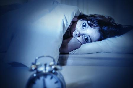 目覚まし時計と目でベッドで若い女性を開く暗いスタジオの照明睡眠と悪夢のような問題の彼の問題について考えて不眠症と睡眠障害に苦しんでい