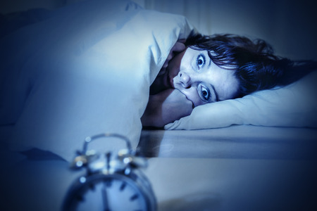problem: young woman in bed with alarm clock and eyes opened suffering insomnia and sleep disorder thinking about his problem on dark studio lighting in sleeping and nightmare issues Stock Photo