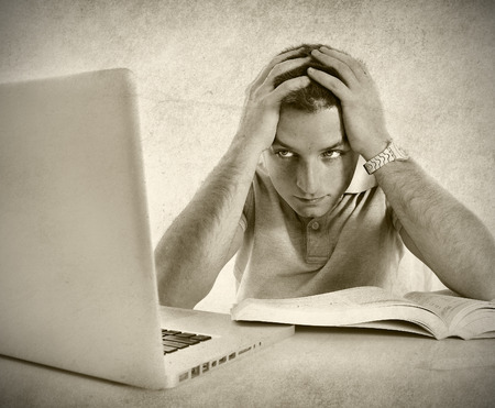 young student man worried frustrated and overwhelmed studying exam with book and computer laptop with hands on head in college education stress on grunge black and white photo