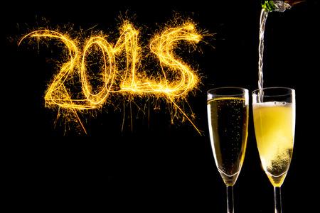 Fles vullen Champagne Glazen voor het vieren oudejaarsavond 2015 met sprankelende bliksem nummers geïsoleerd op zwarte achtergrond als nieuwe jaar wenskaart