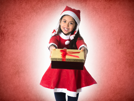 Cute Little Hispanic Girl in Santa Claus costume holding a Christmas Box Present as giving or receiving it on red Xmas studio background photo