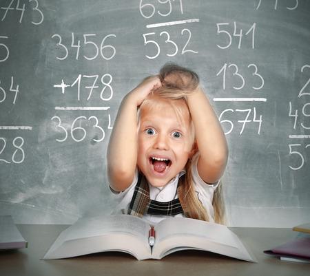 deberes: dulce niña pequeña escuela que tira de su pelo rubio en el estrés volviendo loca con el cálculo matemático estudia hacer la tarea en concepto de educación de los niños en la pizarra llena de números
