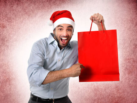 happy man in Santa hat holding and pointing red shopping bag in Christmas consumerism , sale, buying and xmas gifts and presents concept isolated on red studio background photo