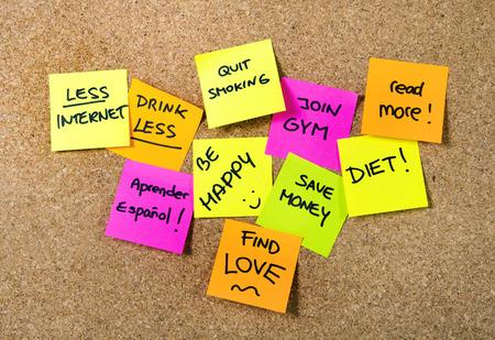 Grupo de resoluciones de año nuevo puesto que las notas en rosa, amarillo, naranja y verde en tarjeta del corcho por escrito con el mensaje de la dieta, se unen gimnasio, encontrar el amor, dejar de fumar y ser feliz Foto de archivo