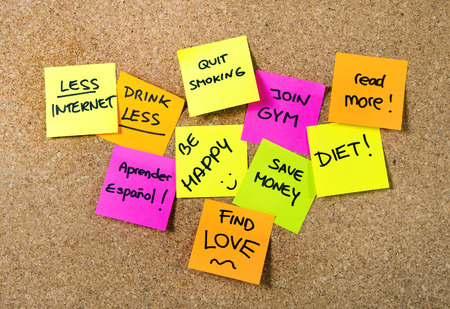 fitness and health: Gruppo del nuovo anno risoluzioni post-it Notes in rosa, giallo, arancio e verde a bordo di sughero scritta con il messaggio di dieta, unire palestra, trovare l'amore, smettere di fumare ed essere felici