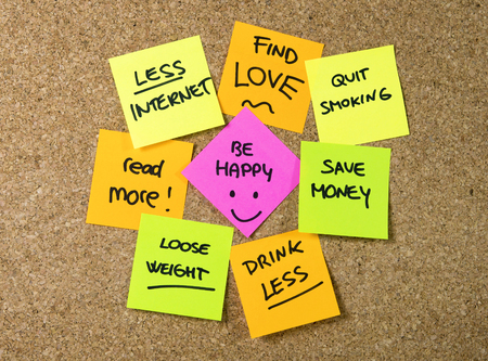 Group of New year Resolutions Post it Notes on pink, yellow, orange and green on cork board written with message of diet, join gym, find love, quit smoking and be happy photo